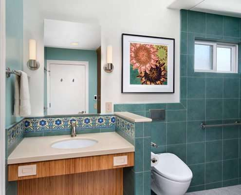 A universal design bathroom inspired by Catalina tiles features a wall-mounted toilet and a roll-under vanity.