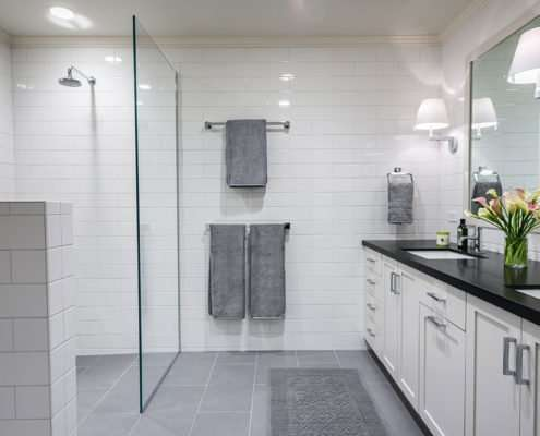 A monochromatic universal design bathroom has a curbless shower with a glass wall and dual sinks.