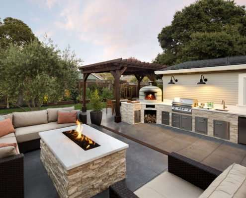Firepit seating area next to outdoor kitchen with grill