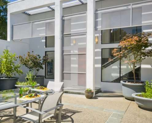 outdoor seating next to glass exterior of house