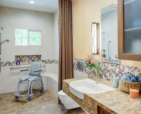 A universal design bathroom with a tiled accent has a roll-under stone vanity, wall-mounted toilet, and curbless shower with a shower wheelchair in it.
