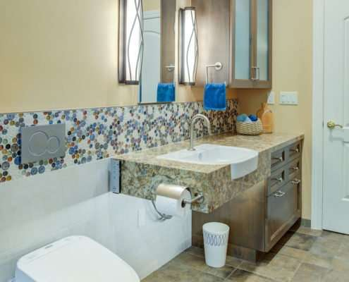 A universal design bathroom with a tiled accent has a roll-under stone vanity and a wall-mounted toilet with a flush plate.