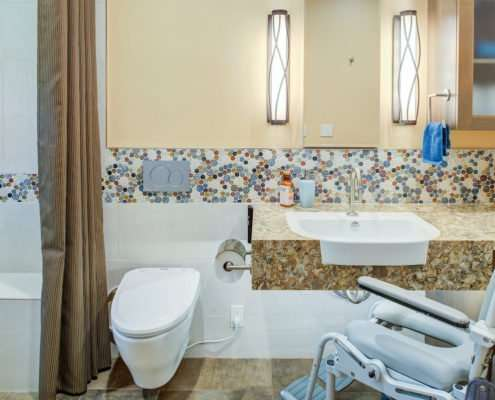 A universal design bathroom with a tiled accent has a roll-under stone vanity, wall-mounted toilet, and curbless shower with a bench.