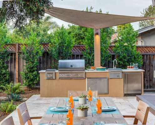 built-in grill next to outdoor kitchen table