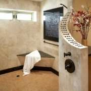 A natural, universal design bathroom features a large, open curbless shower with a bench and brushed handrail in the corner.