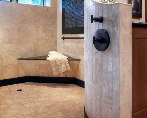 A universal design bathroom has a large, open curbless shower with a bench and brushed handrail in the corner.