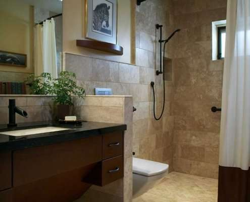A universal design bathroom with a curbless shower with a curved curtain rod, a tankless wall-mounted toilet, and wooden roll-under vanity.