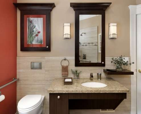 A universal design bathroom has a wall-mounted toilet with a flush plate and roll-under vanity.
