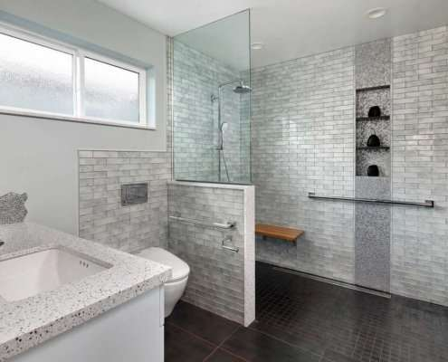 A modern, gray universal design bathroom features a curbless shower and tile details.
