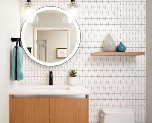 Bright white bathroom with wooden drawers and shelving