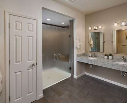 A contemporary universal design bathroom features a curbless shower with closed, frosted glass doors and a roll-under vanity with two sinks.