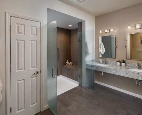 A contemporary universal design bathroom features a curbless shower with open, frosted glass doors and a roll-under vanity with two sinks.