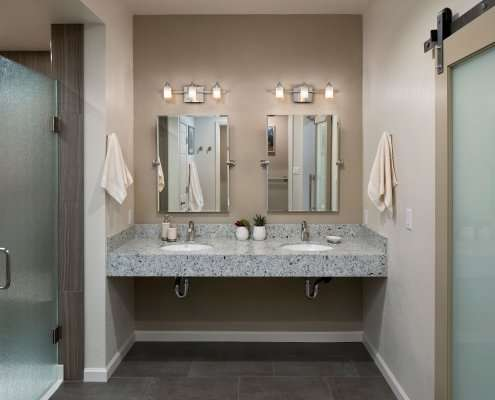 A contemporary universal design bathroom features a dual, roll-under vanity and a curbless shower with frosted glass doors.