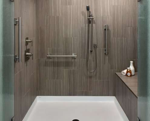 A universal design bathroom has a roll-in shower with brushed silver railings, dual shower heads, and a bench.