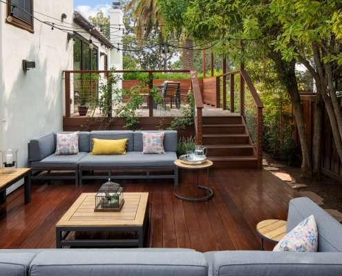 Comfortable couches in outdoor seating area on wooden deck