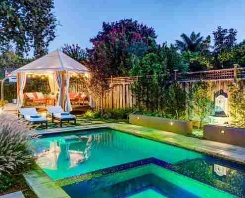 gazebo outdoor seating area next to lit pool