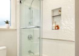 white bathroom and shower with shower shelves